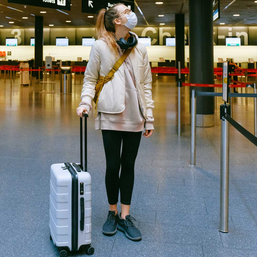A woman wearing a surgical mask, with luggage at a terminal