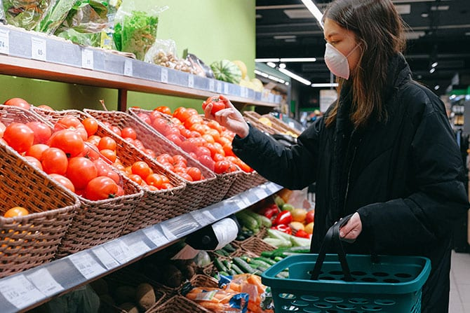 A woman with a surgical mask shopping for food.